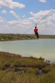 guest riding the zip line from the observation tower over the coba lagoon