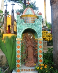 headstone with a religious theme and statue of the virgin de guadalupe