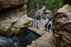 a view from the top where the stream emerges from the cave and flows down to form cascading pools of water