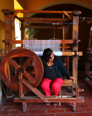 Inside the cultural center, a women demonstrates how to use an antique spinning wheel. A foot powered loom is in the background.