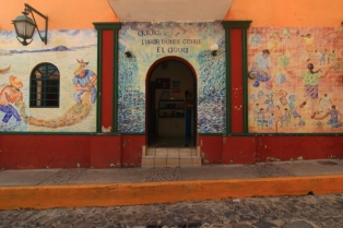 a mural on the front wall of the city hall across from the plaza